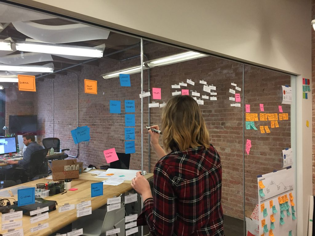 A Grand Studio designer works through ideas on post-its stuck to the wall